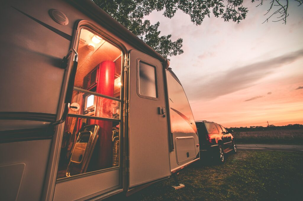 RV with car at sunset.